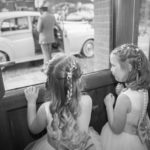 Two bridesmaids looking at Wedding Car
